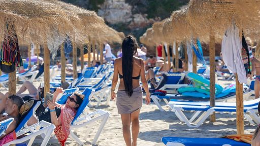 Cover Photo: A photo of a woman with black hair moving between rows and rows of tourists in beach chairs. We can only see her back.