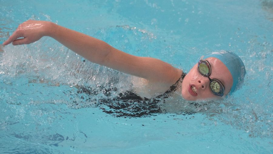 Cover Photo: An image of a young girl swimming in a pool. She wears a light blue swim cap and googles.