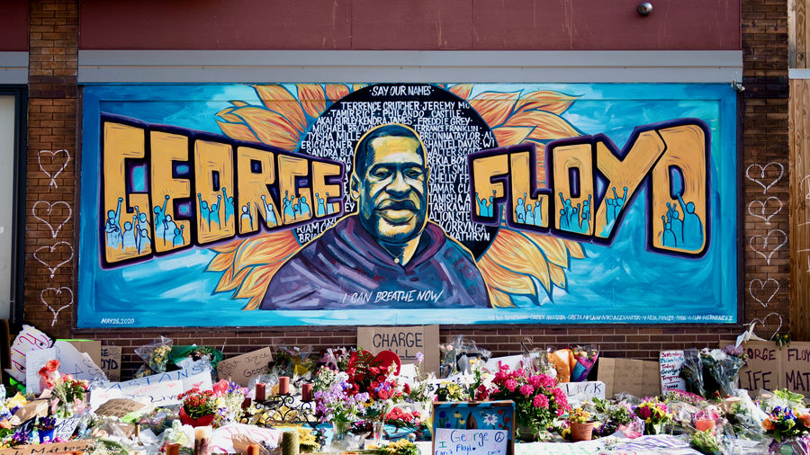 Cover Photo: A Minneapolis mural and memorial honor George Floyd, killed by police on May 25, 2020. The mural is by artists Xena Goldman, Cadex Herrera, and Greta McLain. Flowers, candles, and signs left by mourners in the foreground.