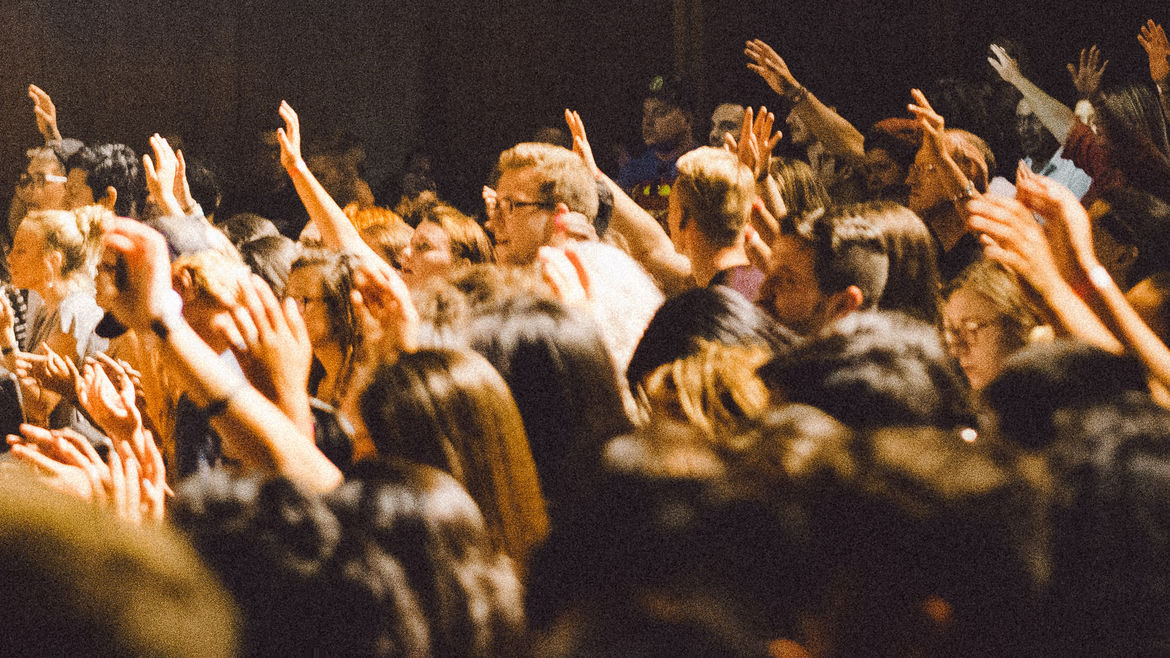 Cover Photo: An image of a crowded event space with multiple people's hands up.