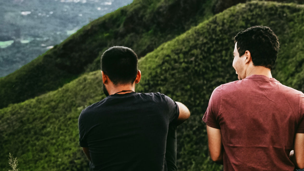 Cover Photo: Two men sit together on a mountain, their backs to the camera.
