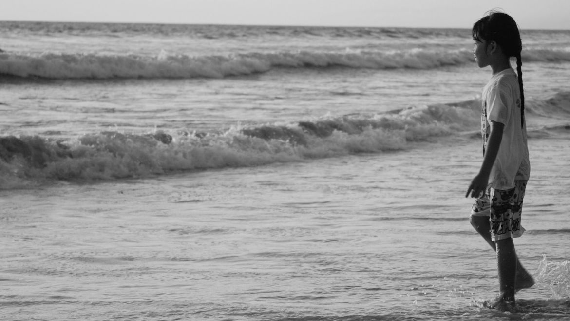 Cover Photo: A black and white photo of a young girl about ten yers old at a beach, t-shirt and shorts wet from the waves, about to walk into the water.
