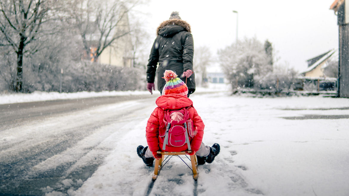Cover Photo: A photo of a snowy day. A woman in a long black coat and heavy winter hood pulls a small child wearing a red coat and matching backpack on a sleigh. They are headed toward a tree-filled road.