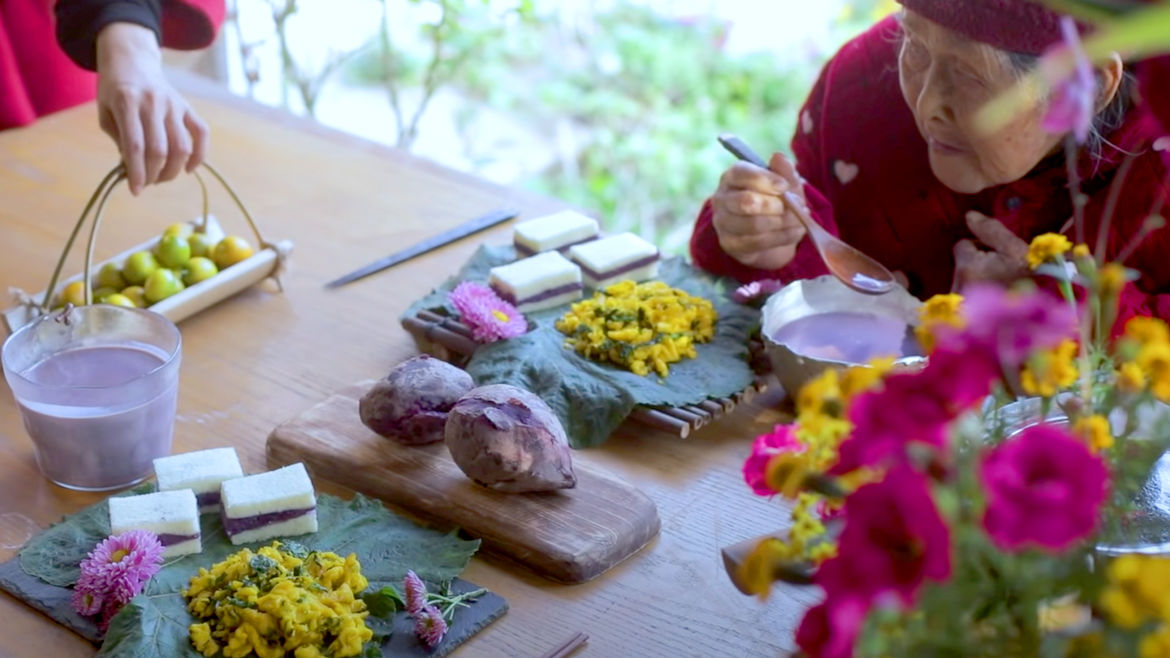 Cover Photo: A screenshot from Liziqi's YouTube video. On the table are purple potatoes, soy milk, steamed rice cakes, fruits, and flowers. An elderly Chinese woman sit as the  table  holding a spoon filled  with some soy milk.