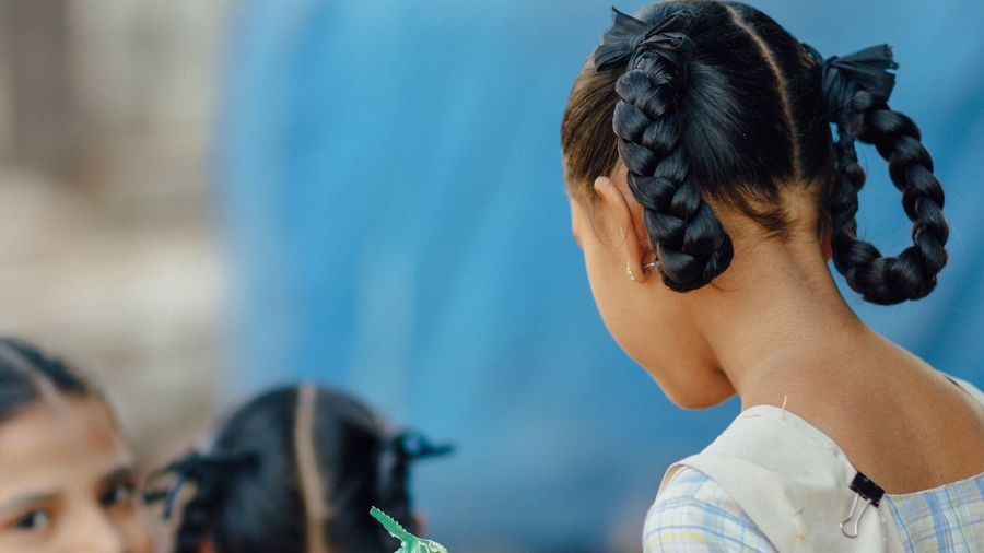 Cover Photo: A photo of three Indian girls, each their hair parted into two extremely tidy braids, looped together with black ribbon.