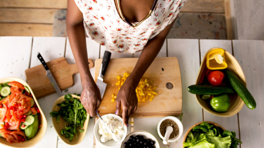 Cover Photo: This photograph shows a Black woman in a kitchen, chopping vegetables. The light is bright and sunny and the image is focused on her hands.