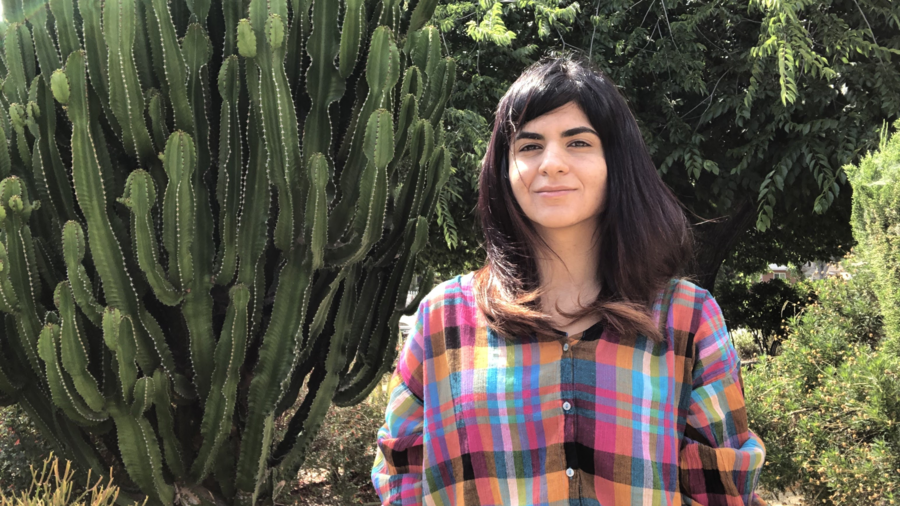 Cover Photo: An image of  artist Maryam Sefati  in a plaid shirt with a cactus behind her