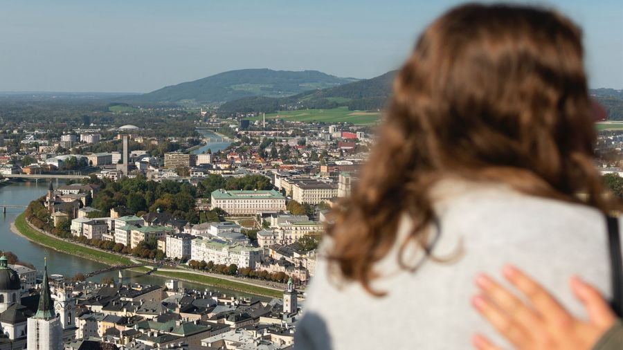 Cover Photo: This photograph is taken from a high point and overlooks the picturesque Salzburg, Austria. A brown-haired woman is in the foreground of the photo, and she is a bit blurry, as if she is in the middle of turning away from the view and turning to talk to a friend.