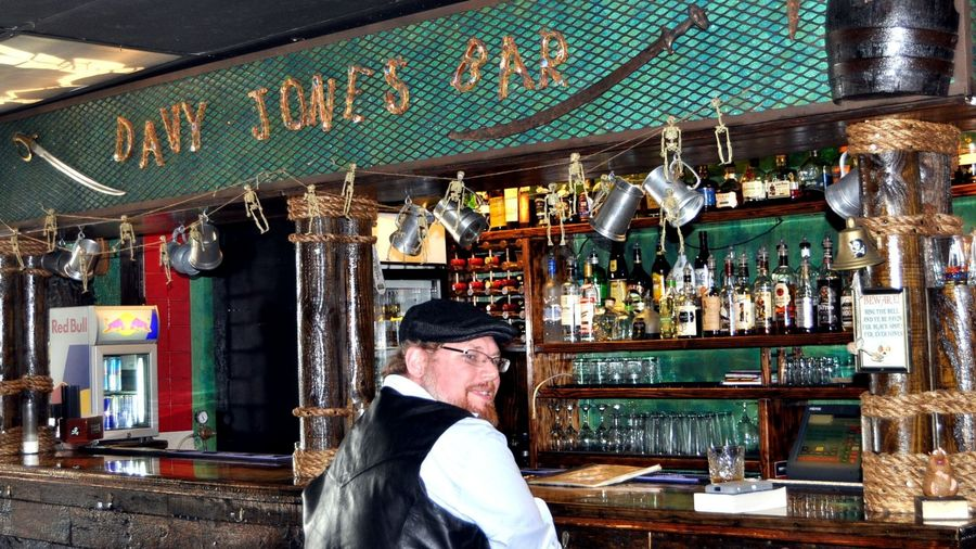 "Cover Photo: A photo of an old-fashioned bar. On a green awning over the bar, the words ""DAVY JONES BAR"" are spelled in gold letters across a green background. A sword, barrel, and tiny skeletons decorate its corners. Vintage tankards hang where glasses would be. A single man sits on a stool in front of it."