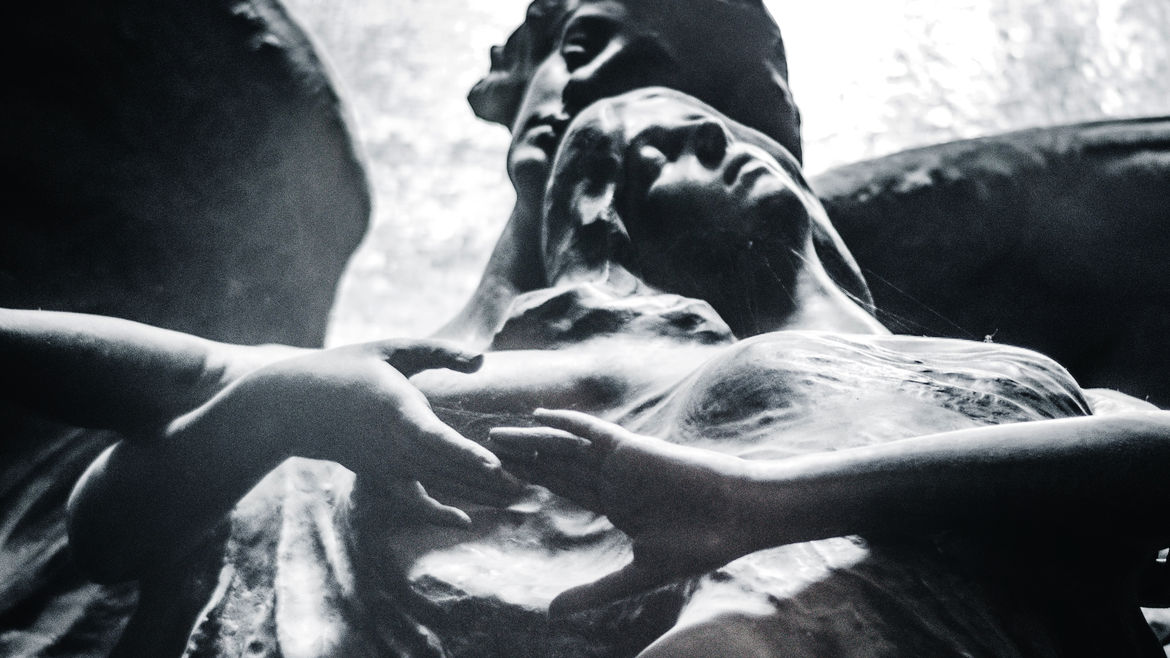Cover Photo: A black and white photo of two statues: angels caught in what seems like an intimate embrace.