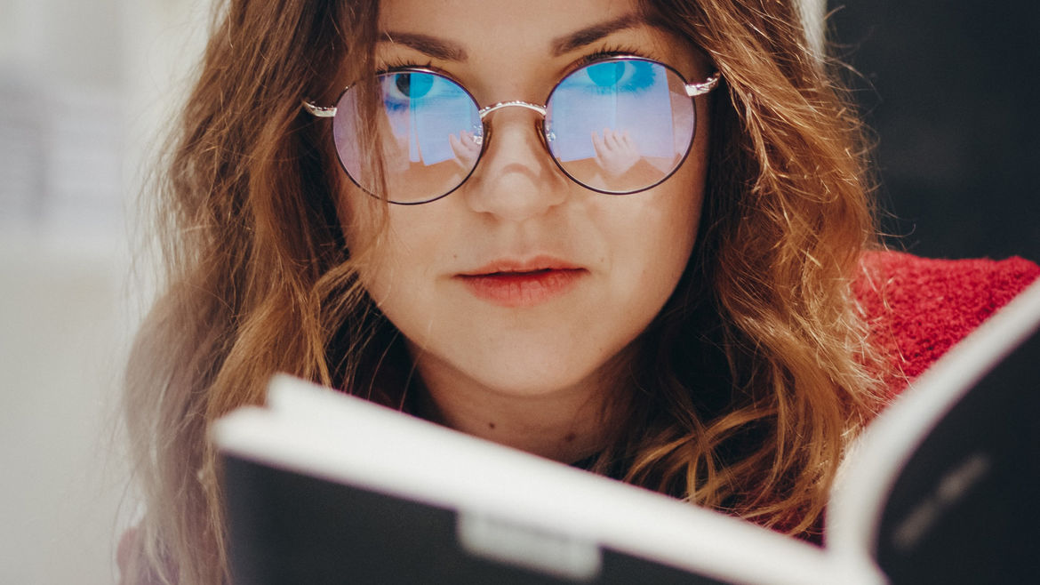 Cover Photo: A woman holds a book; reflected in each lens of her glasses, the viewer can see her hand holding the book.