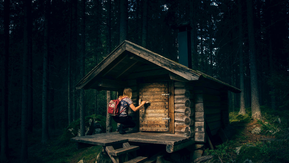 Cover Photo: A photo of a forest made of tall trees, and a woman kneeling in front of a tiny cabin's door, making herself small enough to fit inside.