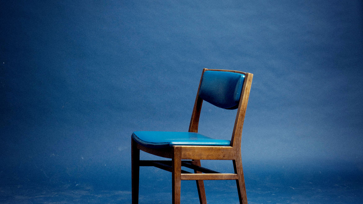Cover Photo: A wooden chair with a blue seat stands alone in a blue room.