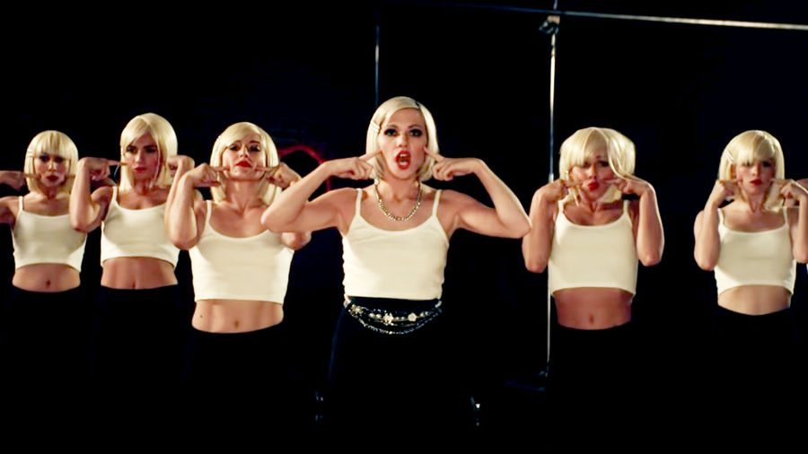 "Cover Photo: A still from the music video for Carly Rae Jepsen's ""Too Much."" Six different Carlys wearing a white tank top and black jeans stand against a black background, putting their fingers to their cheeks."