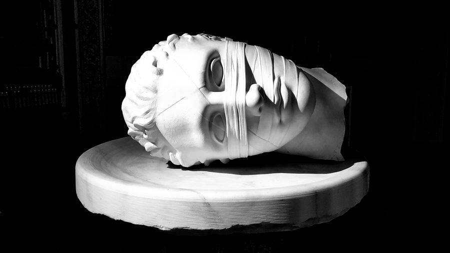 Cover Photo: white marble sculpture of a bandaged, severed head (intended to be John the Baptist) resting on a plate