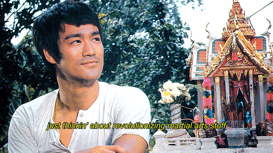 "Cover Photo: A photo of Bruce Lee standing in front of a shrine with his arms crossed, a happy, approving, and serene smile is on his face. The subtitle says: ""Just thinkin' about revolutionizing martial arts stuff."""