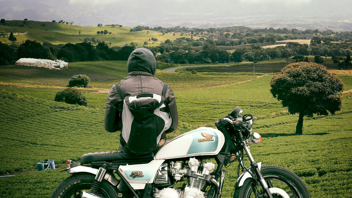 Cover Photo: In this photograph, a man in a hoodie and a leather jacket leans on his fashionable-looking motorcycle as he looks out over a misty green valley spotted with trees