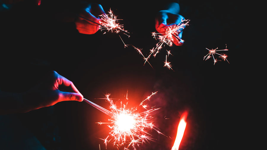 Cover Photo: A close-up of three or four people's hands in the darkness, each holding sparklers that light up the center of the photo.