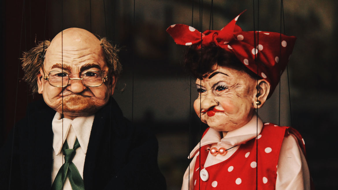 Cover Photo: A photo of two very realistic puppets—an old man in a suit and green tie, and an old woman in a red dress and red polka dot bandana. They are both disgruntled.