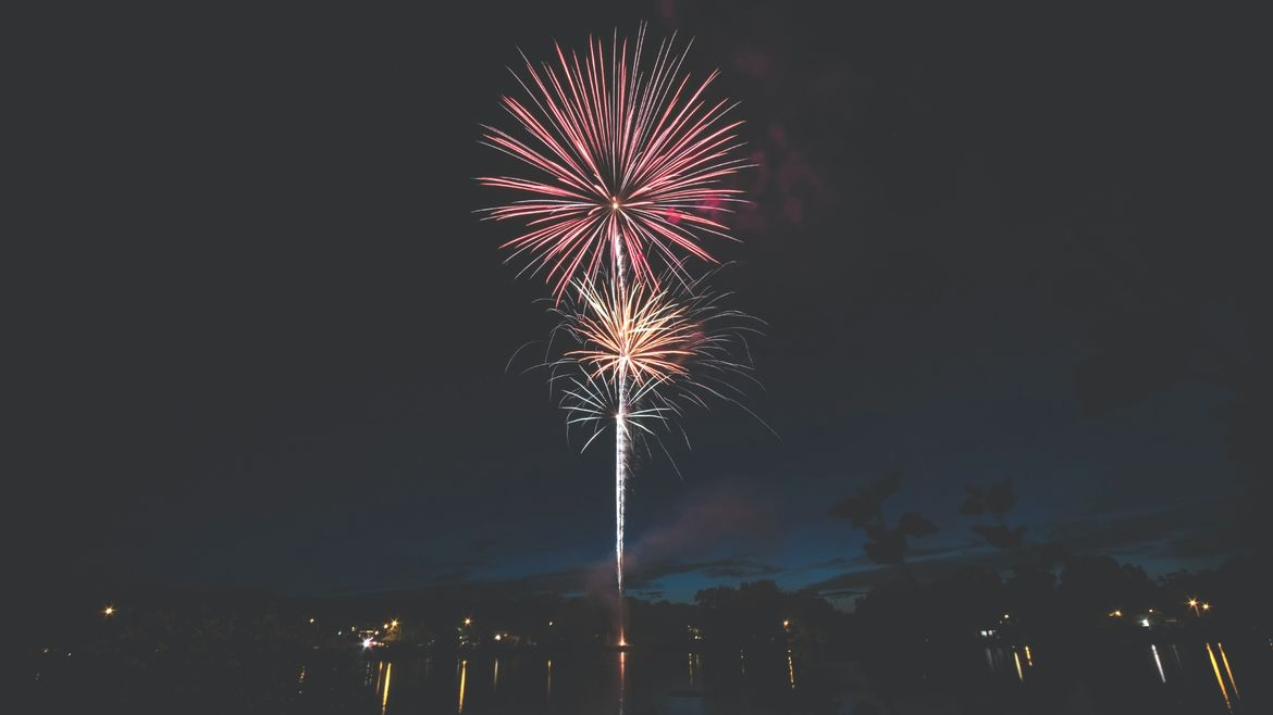 Cover Photo: red and gold fireworks exploding in the night sky, over a dim body of water with small yellow and white lights reflecting on the surface