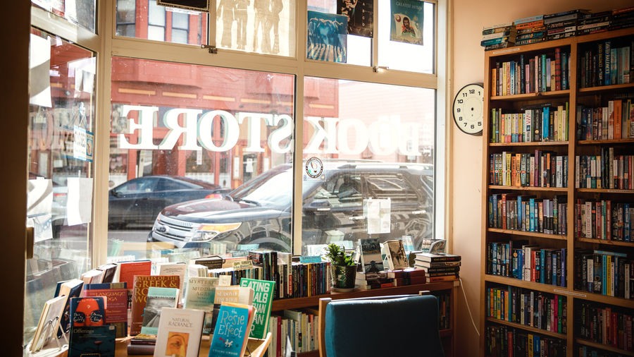 Cover Photo: city bookstore window viewed from the inside, with tall bookshelves on the far right and shorter ones in the foreground, alongside a blue chair