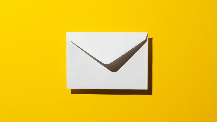 Cover Photo: A white envelope sits in the middld of a bright yellow background.