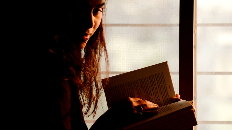 Cover Photo: An image of a woman reading half of her face in a shadow as the light shines in through the window