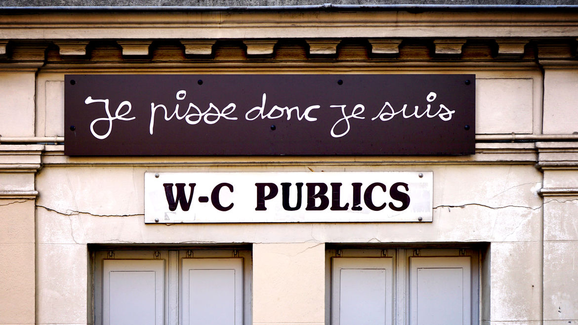 "Cover Photo: An image of a public restroom building with a sign that read ""je pisse donc je suis"" and a sign below that reads ""W-C PUBLICS"""