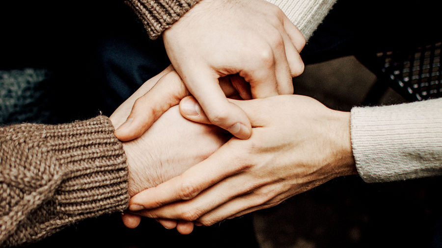 Cover Photo: a pair of hands holding another pair of hands; the gender of the subjects is indeterminable