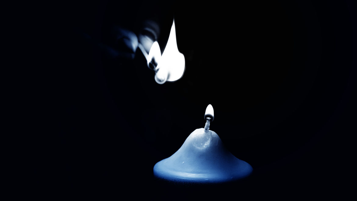 Cover Photo: In this close up photo of a candle,  we see a thick blue candle and it's tiny blue flame, and a thick wisp of white smoke fading into the black background.