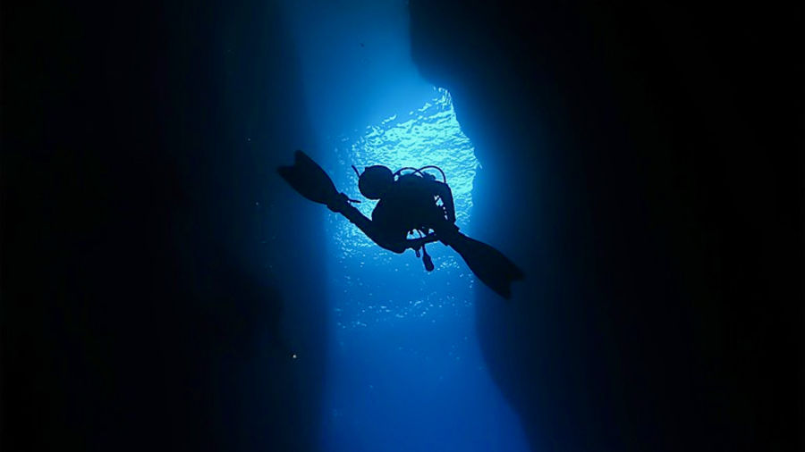 Cover Photo: photograph of a scuba-diver ascending in a blue-lit column between two massive black shapes that might be underwater rocks