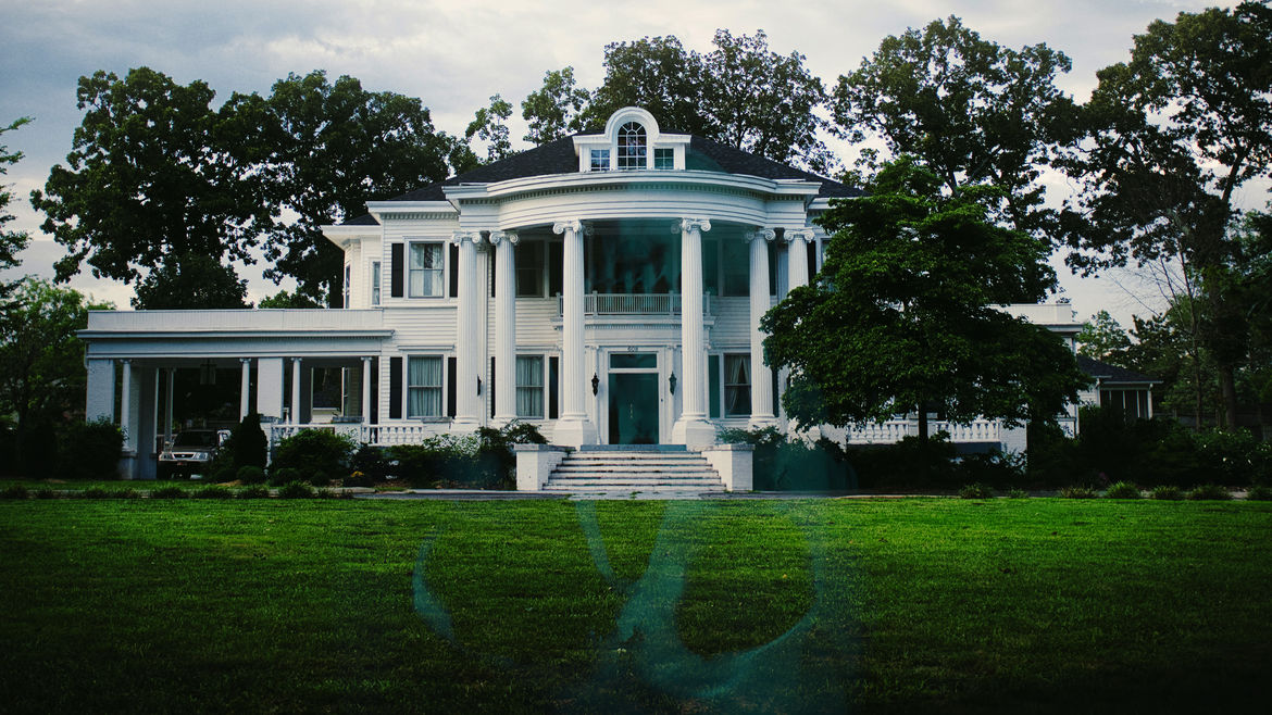 Cover Photo: A photo of a stately, empty, plantation house and its grounds, covered in the shadowy wisp of a green skull.
