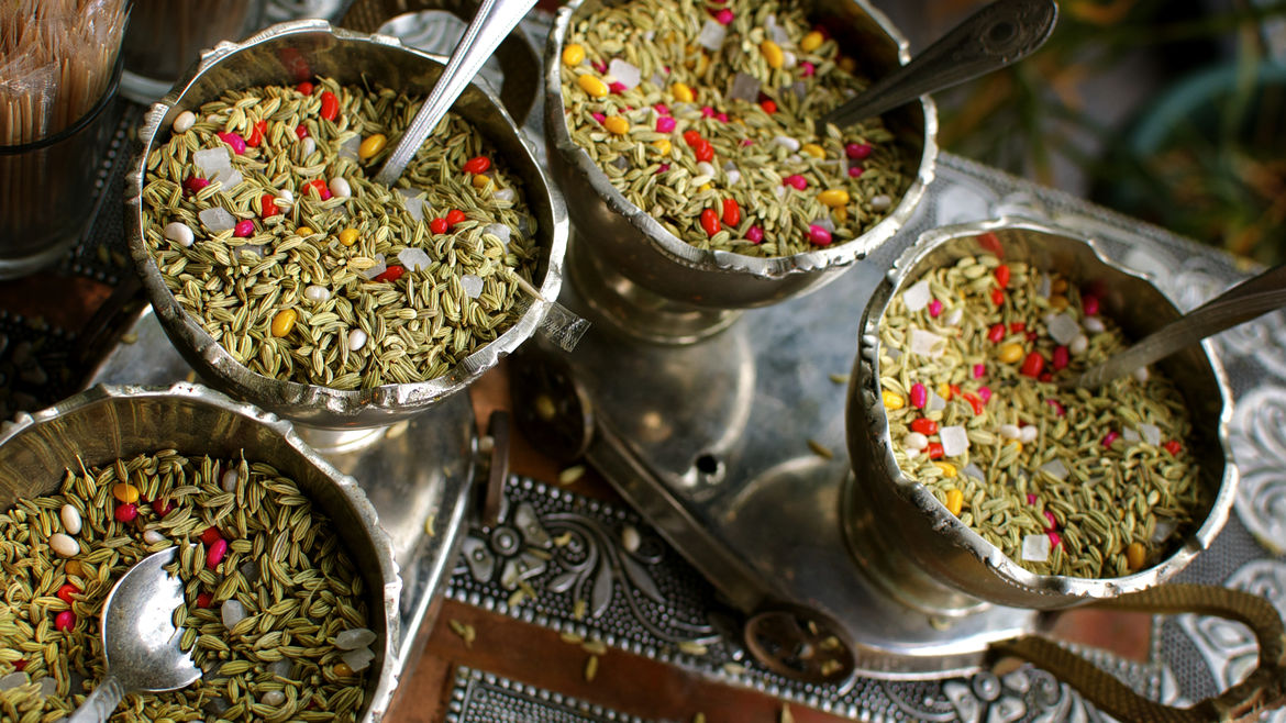 Cover Photo: bowls of fennel candy also known as saunf with silver spoons in them
