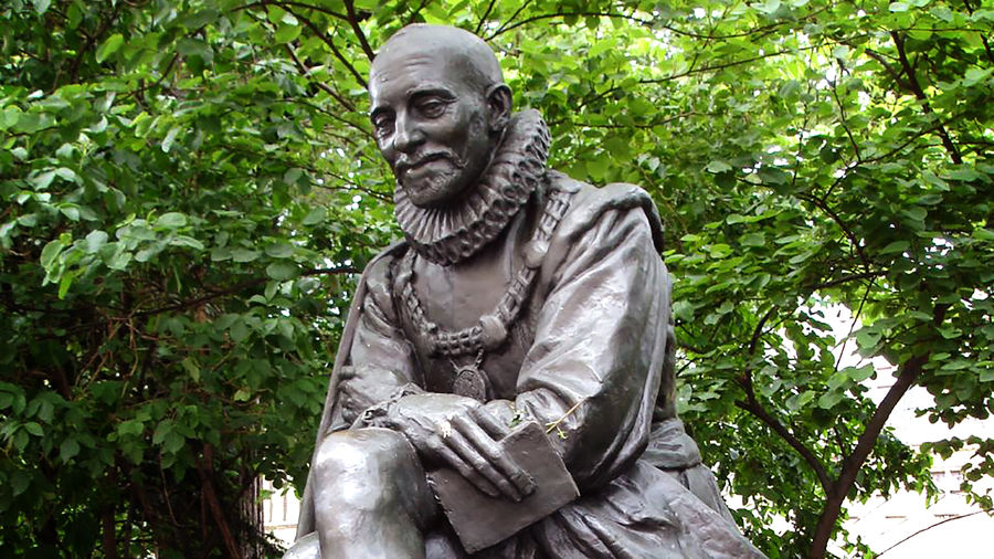 Cover Photo: a grey-brown bronze statue of Michel de Montaigne, depicted here as an aging man with a bald head, a mustache, and short beard, wearing a neck ruff, robes, and a chain of office