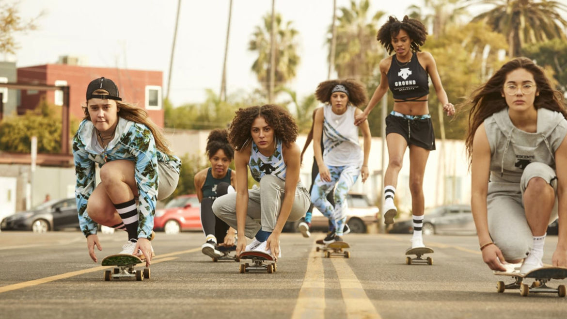 Cover Photo: In this still from HBO's TV series 'Betty,' a collection of women skateboard down the middle of a wide street framed with palm trees and washed in a yellow, California light. They are a racially diverse crew and all of them look like they are taking their sport seriously