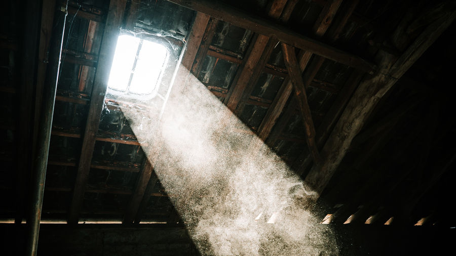 Cover Photo: This photograph shows an attic window beaming into a dusty room. The rafters are dark and there are some spiderwebs, as if the room isn't heavily used.