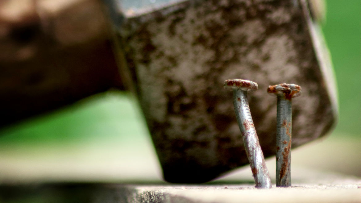 Cover Photo: In the foreground, two rusty nails are hammered into a plank of wood; in the background, a mallet rests behind them