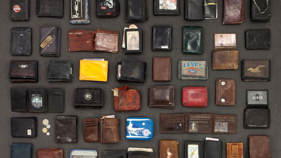 "Cover Photo: A photo of many wallets of different size and color taken away from immigrants at the border, deemed ""unnecessary"" an item."