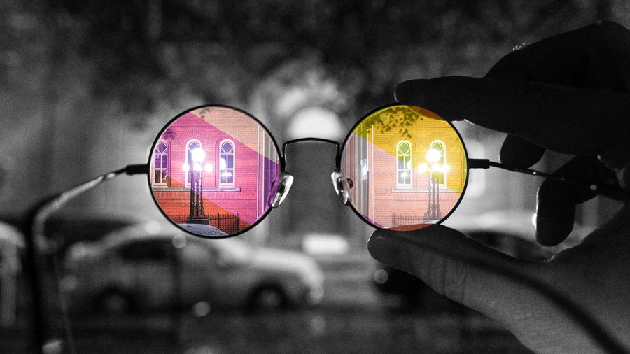 Cover Photo: A black-and-white photo of someone holding up a pair of glasses at eye level, facing the street. In the lenses, the world appears in color.