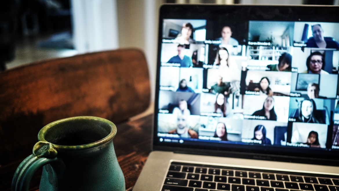 Cover Photo: An image of a mug and a computer screen in the background with a zoom meeting