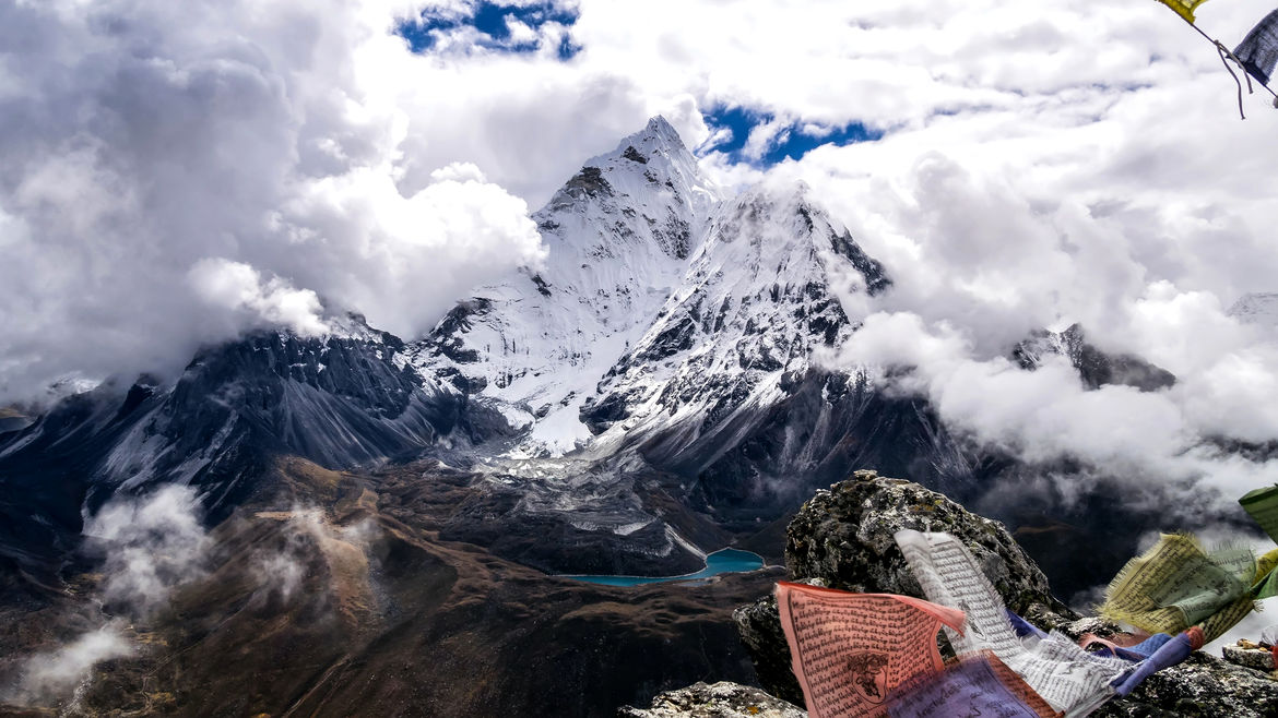 Cover Photo: snow-capped Mt. Everest wreathed in white clouds, with just a few fluttering prayer flags in the foreground