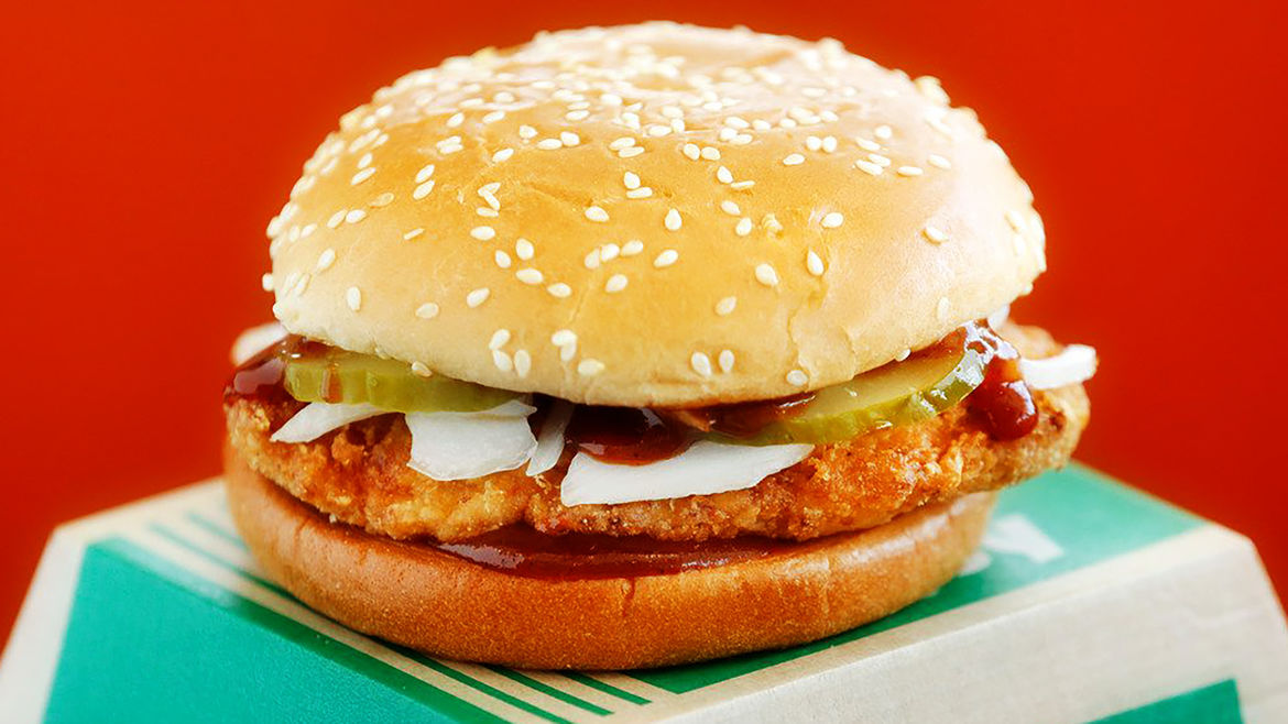 Cover Photo: A bright promotional photo of a Spicy McChicken Sandwich agains a red background.