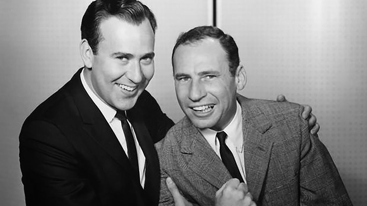 Cover Photo: A photo of Mel Brooks and Carl Reiner leaning in close and looking at the camera. They are both smiling, but Carl's smile is one famously used for one of their comedy bits.