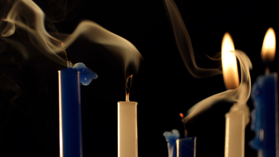 Cover Photo: closeup photograph of three blue and two white Chanukah candles against a black background; two tapers lit, three recently extinguished with smoke trails rising