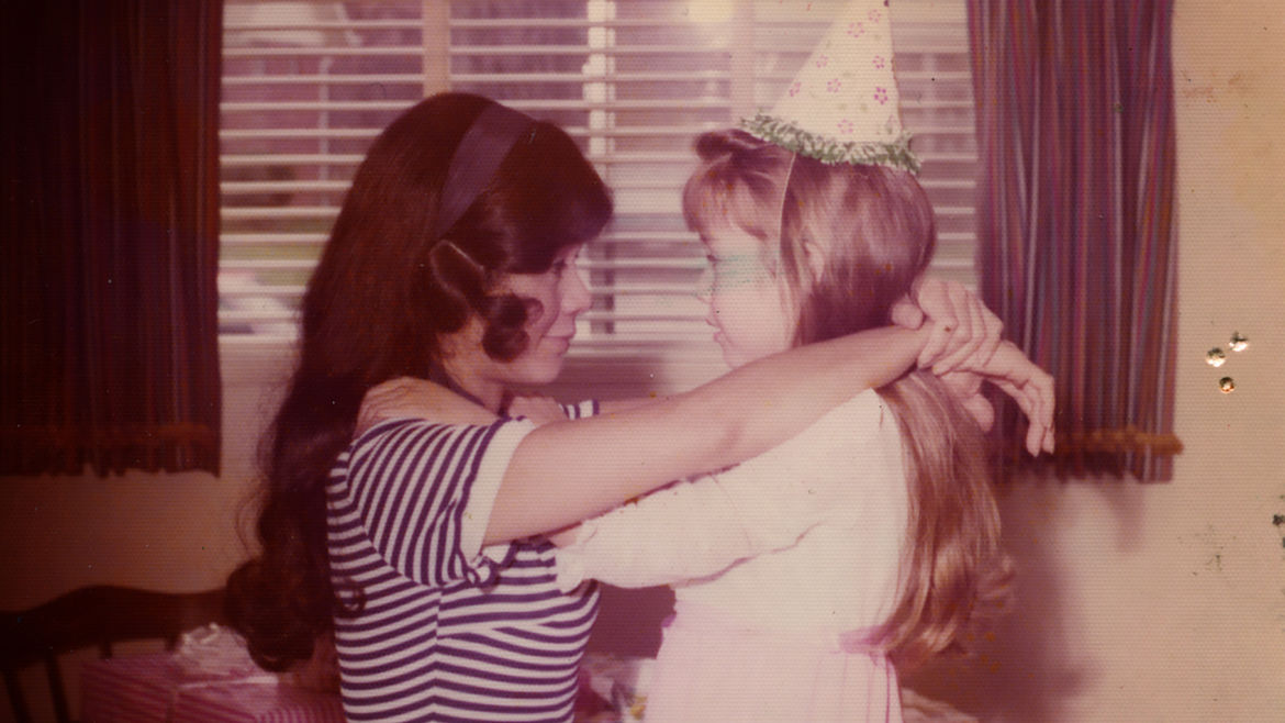 Cover Photo: An image of the author on her birthday as a child. She and her mother rest their arms on each other's shoulders and are looking at each other.