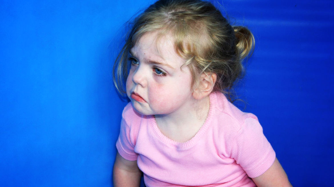 Cover Photo: A small girl with blonde hair and deep blue eyes frowning tearfully, as if angry or about to cry.