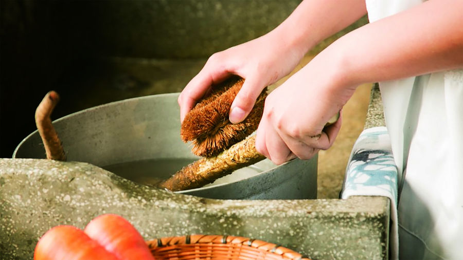 Cover Photo: A pair of hands cleaning a pot with a Kamenoko Tawashi, or a turtle brush—it is made out of natural fibers, resembling a fuzzy donut