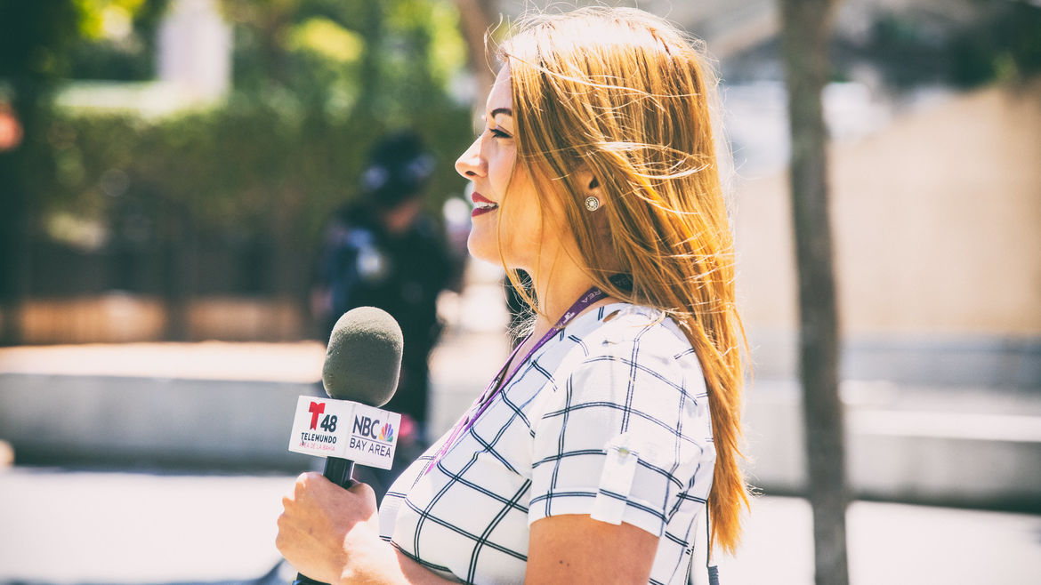 Cover Photo: A reporter wearing red lipstick, turned away from the photographer's camera, looking into what might be a news camera. She's holding a microphone with the Telemundo and NBC logos on each side.