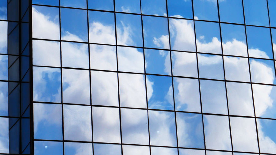 Cover Photo: In this photograph, we see blue sky and white cottony clouds reflecting off a tall, glassy office building. The imagine is divided into a checkerboard because of the window frames.