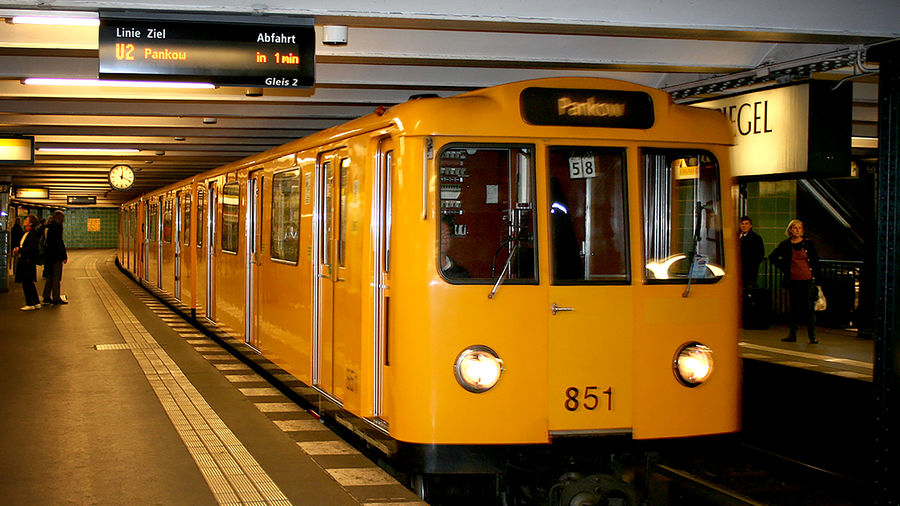 Cover Photo: In this photograph, we see a yellow U-Bahn train pulling into a Berlin platform. There are a few people standing on the warmly lit platform, but not many.